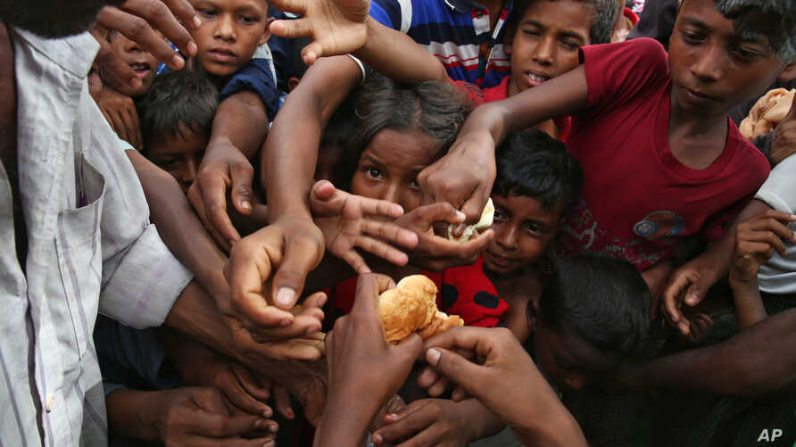Rohingya Muslim children, who fled Myanmar,  stretch their hands out to receive food distributed by locals at the Kutupalong makeshift refugee camp in Cox's Bazar, Bangladesh, Aug. 30, 2017.