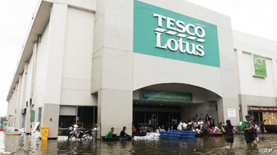Thai residents wade through floodwaters to buy food at a hypermarket in Bangkok, Thailand, October 27, 2011.