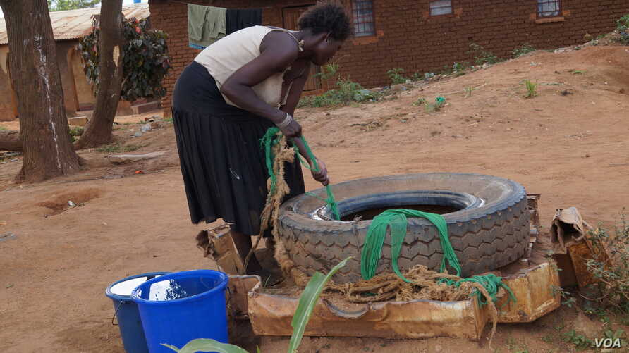 A woman draws water from an unprotected well in Chigwirizano, a peri-urban area hit by a Cholera outbreak in Malawi. (Photo: Lameck Masina for VOA)