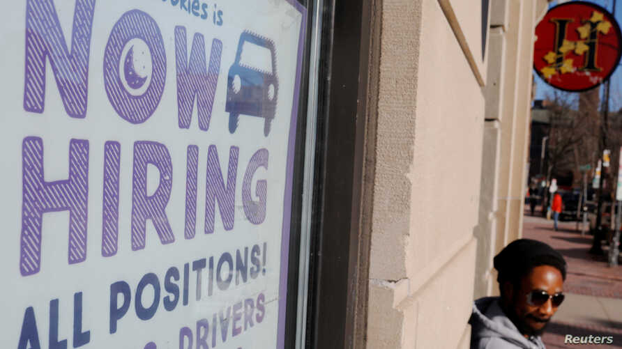 """FILE - A """"Now Hiring"""" sign sits in the window of Insomnia Cookies in Cambridge, Massachusetts, Feb. 11, 2019."""