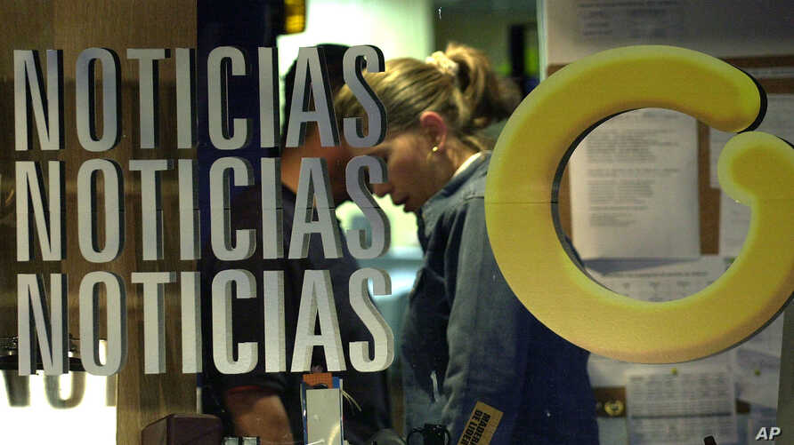 """FILE - An employee at Globovision, a 24-hour television news channel, works behind a glass reading """"News"""" with Globovision's logo """"G"""" at the channel's headquarters in Caracas, Venezuela, Oct. 3, 2003."""