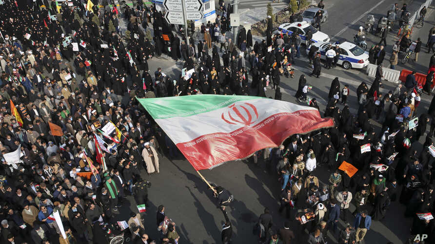 In this photo provided by Tasnim News Agency, a demonstrator waves a huge Iranian flag during a pro-government rally in the northeastern city of Mashhad, Iran, Jan. 4, 2018.