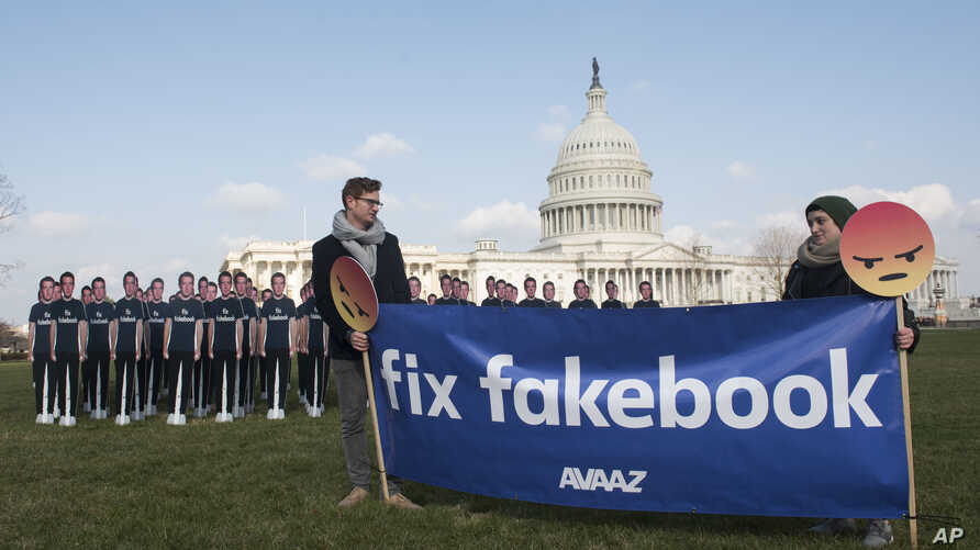 Avaaz campaigners hold a banner in front of 100 cardboard cutouts of Facebook CEO Mark Zuckerberg outside the U.S. Capitol in Washington, April 10, 2018, ahead of his Senate testimony. Avaaz, an advocacy group, is calling attention to hundreds of mil...