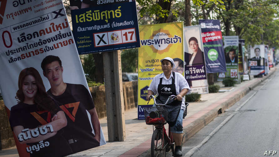 A woman rides a bicycle past electoral posters in Bangkok on March 17, 2019, ahead of the March 24 general election.
