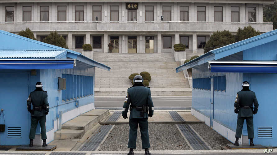 FILE - In this March 12, 2014 photo, a North Korean soldier, center top, looks at the southern side as three South Korean soldiers guard at the border village of Panmunjom, which has separated the two Koreas since the Korean War, in Paju, South Korea