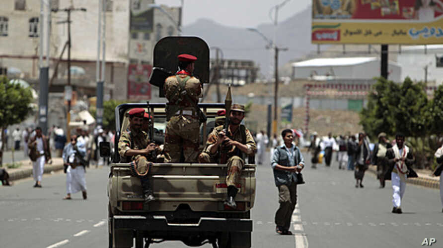 Army soldiers stand guard in a truck as anti-government protesters take part in a demonstration demanding the ouster of Yemen's President Ali Abdullah Saleh in Sana'a, June 3, 2011