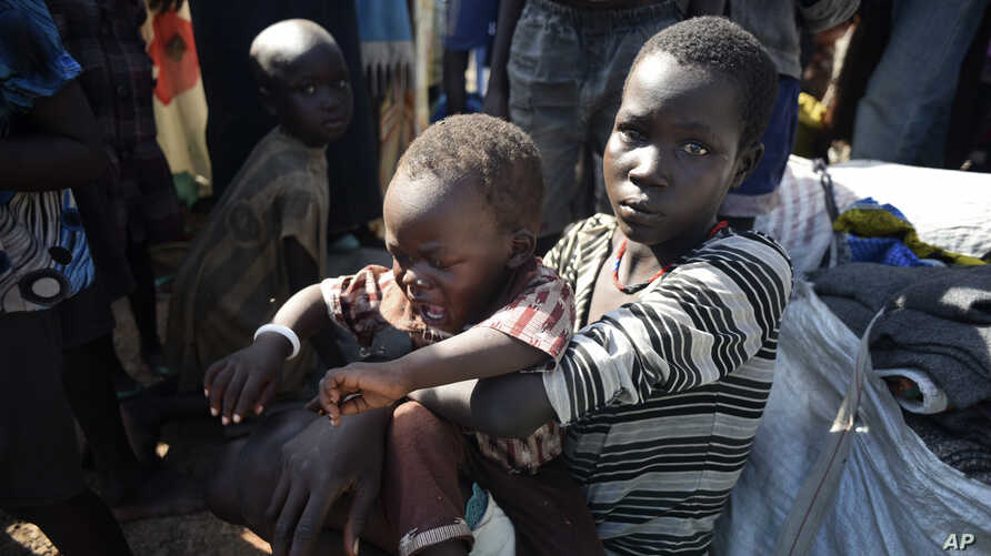 In this photo taken Monday, June 29, 2015, a newly-arrived displaced woman holds a child as they sit in the UN base in Bentiu, South Sudan.