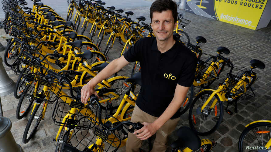Ofo France general manager Laurent Kennel poses with city bike-sharing service Ofo bicycles at Autonomy and the Urban mobility summit in Paris, France, Oct. 19, 2017.
