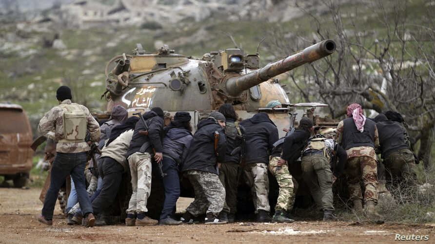 Fighters from the Suqour al-Sham Brigade, which is part of the Free Syrian Army, take cover from snipers behind a tank during what activists said were clashes with forces of Syria's President Bashar al-Assad, in the al-Arbaeen mountain area of wester