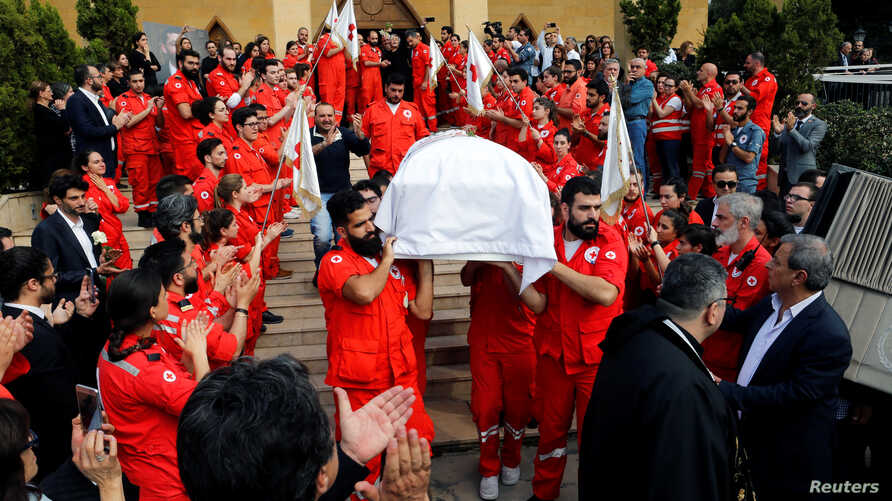 FILE - Members of Lebanese Red Cross carry a coffin of Hanna Lahoud, who was killed in Taiz in southwestern Yemen by unknown gunmen who opened fire on the International Red Cross car, during a mass funeral in Zouk Mosbeh, Lebanon, April 28, 2018.