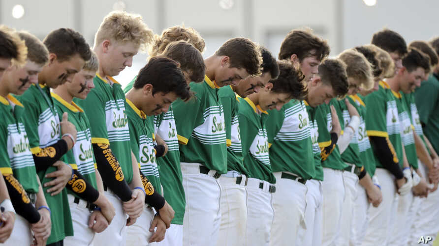 Santa Fe High School baseball players bow their heads in a moment of silence for the shooting victims at their school before a baseball game against Kingwood Park High School in Deer Park, Texas, May 19, 2018.