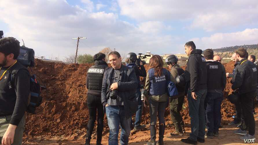 Reporters hurry up what looks to be a berm with views of mountainsides controlled by apposing militaries on Feb. 1, 2018 in Marin, Syria. (H.Murdock/VOA)