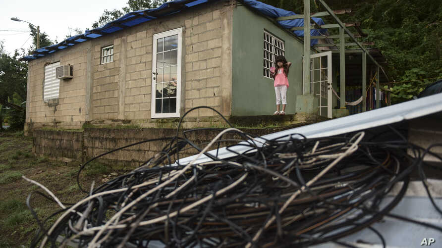 In this Dec. 22, 2017 photo, Melanie Oliveras González stands on the porch of her house, behind a handful of electric cables knocked down by the winds of Hurricane Maria, in Morovis, Puerto Rico.