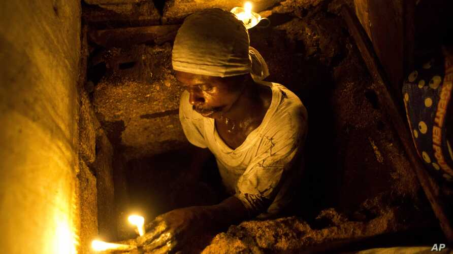 """FILE - Dieusel Gerlin, a""""bayakou,"""" or waste cleaner, uses candles for illumination before descending into the pit of an outhouse in Port-au-Prince, Haiti, Dec. 22, 2016."""