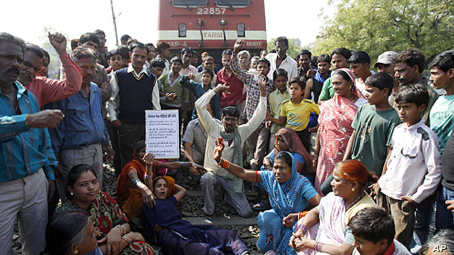 Survivors of the Bhopal gas tragedy and other supporters shout slogans as they lie on a railway track to stop train movement during a protest on a railway track in Bhopal, India, Saturday, Dec. 3, 2011.