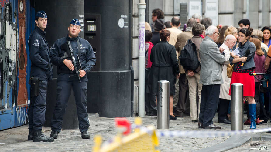 Policemen guard the Jewish museum as people queue for the re-opening ceremony of the museum in Brussels, Belgium, Sept. 14, 2014.