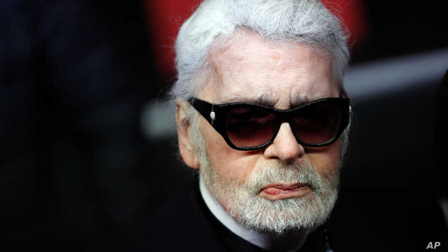 FILE - Fashion designer Karl Lagerfeld poses during the Champs Elysee Avenue illumination ceremony for the Christmas season, in Paris.  Nov. 22, 2018.