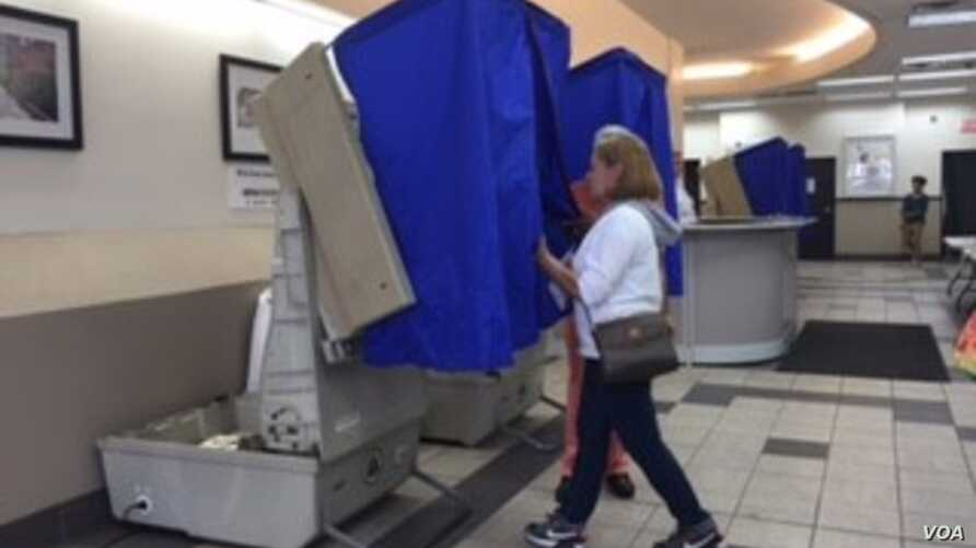 A woman enters a curtained voting machine at a polling station, in Philadelphia, Pa., April 26, 2016. Pennsylvania is one of five Northeast U.S. states voting in presidential primaries Tuesday.