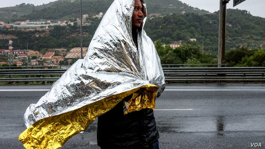 A man from Eritrea walks along the road after leaving a Red Cross Caritas camp set up for migrants in the Italian border town. Hundreds of migrants stay in the town for  a few weeks at a time while trying to cross the border into France. But with eme
