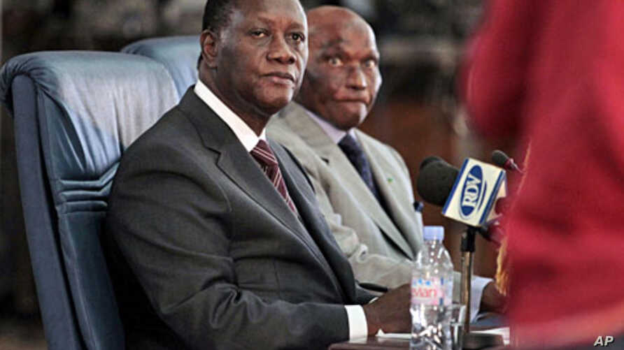 Ivorian President Alassane Ouattara (L) and Senegalese counterpart Abdoulaye Wade listen to a question during a joint press conference in Dakar, May 13, 2011