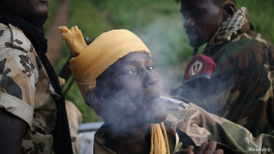 FILE - A Seleka fighter smokes during a patrol, close to the border of the Democratic Republic of Congo June 10, 2014.