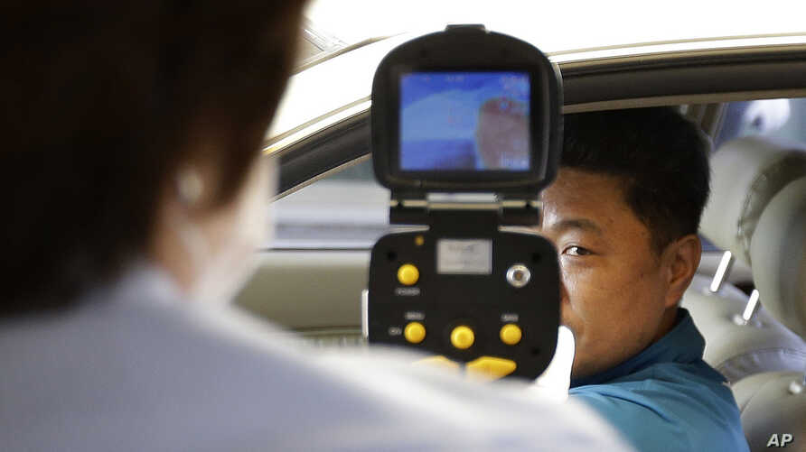 FILE - A South Korean official, left, uses a thermal camera to checks the body temperature of a driver as a precaution against Middle East Respiratory Syndrome (MERS) after he returned from Kaesong, North Korea, near Panmunjom, South Korea, June 13,