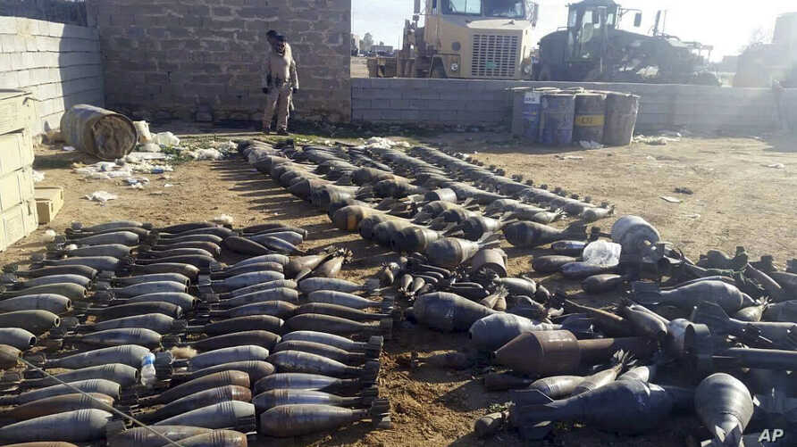 Weapons and explosives confiscated by Iraqi security forces from Islamic State militants are on display at an Iraqi army base as security forces advance their position in northern Ramadi, west of Baghdad, Iraq. Iraqi forces on Tuesday reported progre...