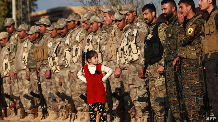 A young girl stands in front of fighters from the Syrian Democratic Forces as they attend the funeral a fellow fighter killed in Hajin during battles against the Islamic State group, in the Kurdish-controlled city of Qamishly in northeastern Syria, D