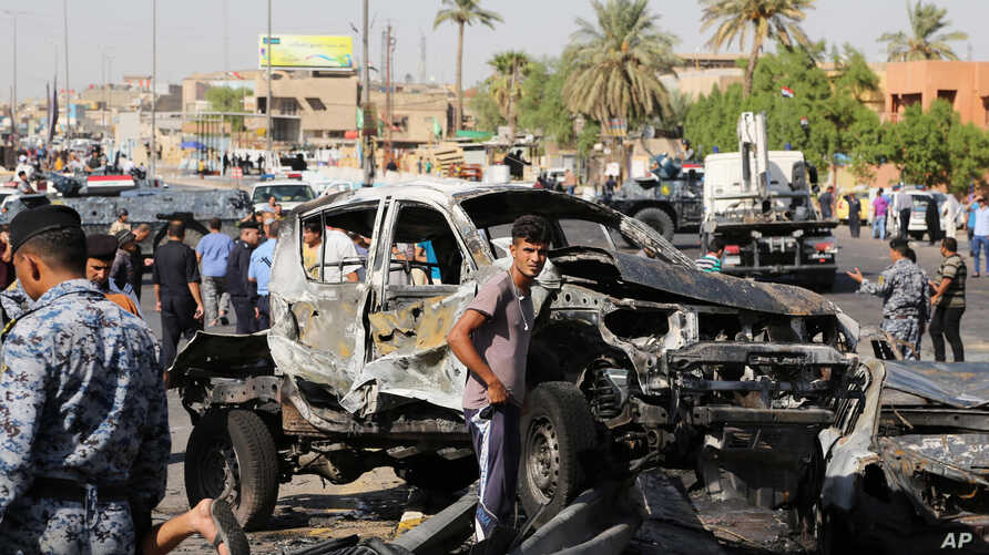Civilians and security forces inspect the site of a car bomb explosion in the southeastern neighborhood of New Baghdad, Iraq, Wednesday, Sept. 10, 2014. Twin car bombs hit near markets in Baghdad killed and wounded dozens of people, Iraqi officials s