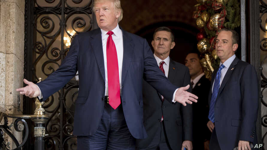 President-elect Donald Trump, left, accompanied by Trump Chief of Staff Reince Priebus, right, and Retired Gen. Michael Flynn, a senior adviser to Trump, center, speaks to members of the media at Mar-a-Lago, in Palm Beach, Fla., Dec. 21, 2016.