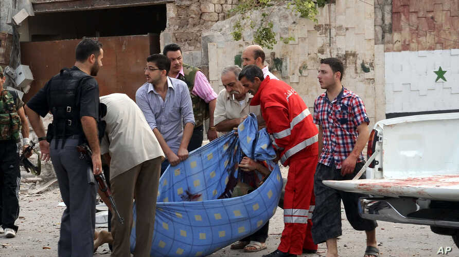 Photo released by the Syrian official news agency SANA, Syrian men carry a dead body at the scene where triple bombs exploded at the Saadallah al-Jabri square, in Aleppo, Syria, October 3, 2012.