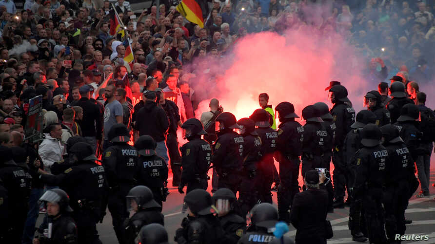 Riot policemen stand guard as the right-wing supporters protest after a German man was stabbed last weekend in Chemnitz, Germany, Aug. 27, 2018.