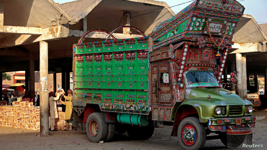 Workers unload fruit from a decorated truck at the wholesale produce market in Faisalabad, Pakistan, May 4, 2017.