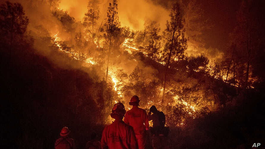Firefighters monitor a backfire while battling the Ranch Fire, part of the Mendocino Complex Fire, on Aug. 7, 2018, near Ladoga, Calif.