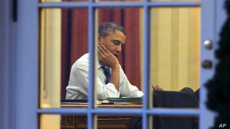 President Barack Obama works at his desk in the Oval Office of the White House in Washington, Jan. 27, 2014, ahead of Tuesday night's State of the Union speech.