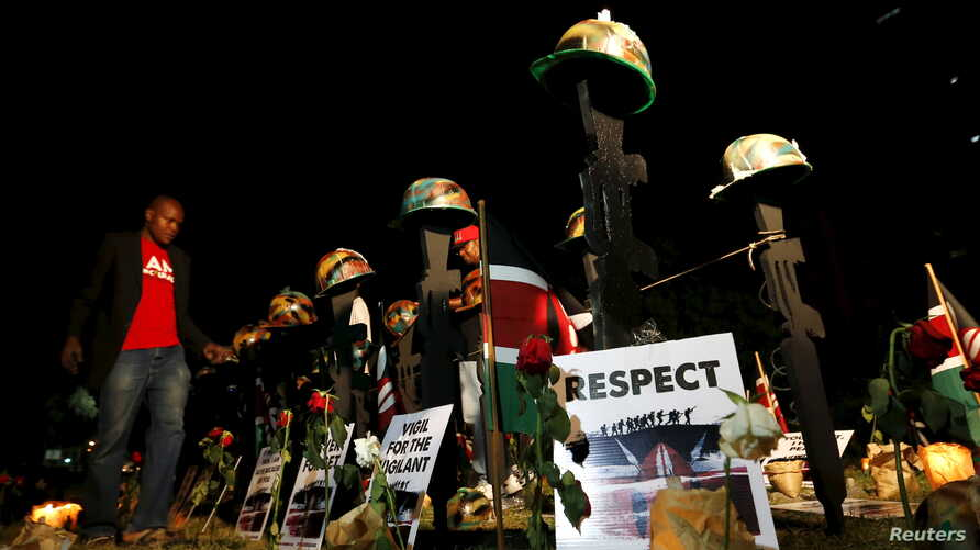 "A volunteer arranges replicas of guns and helmets placed on the ground to symbolize Kenyan soldiers serving in the African Union Mission in Somalia (AMISOM) who were killed during an attack January 15, at a memorial vigil within the ""Freedom Corner"""