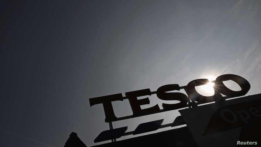 FILE - The signage of Tesco Extra is silhouetted against the sun in southwest London.