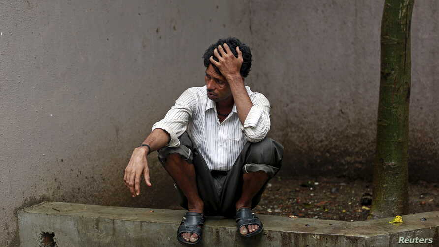 FILE -  Indarlal waits to collect the body of his brother Rajesh, 30, who died after consuming bootleg liquor at a hospital in Mumbai, India, June 21, 2015.