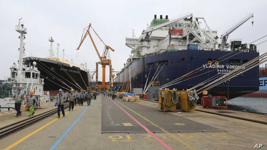 Workers walk past large-sized liquefied natural gas (LNG) carriers under construction at the Daewoo Shipbuilding and Marine Engineering facility in Geoje Island, South Korea,  Dec. 7, 2018.