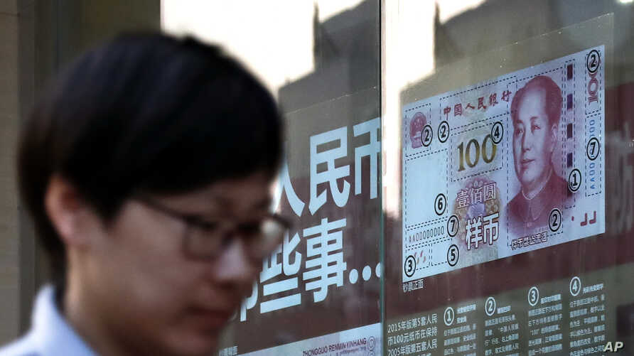 A pedestrian passes by a bank window panel displaying the security markers on the latest renminbi banknote in Beijing, Feb. 27, 2017. China has raised interest rates on short-term loans for the third time.