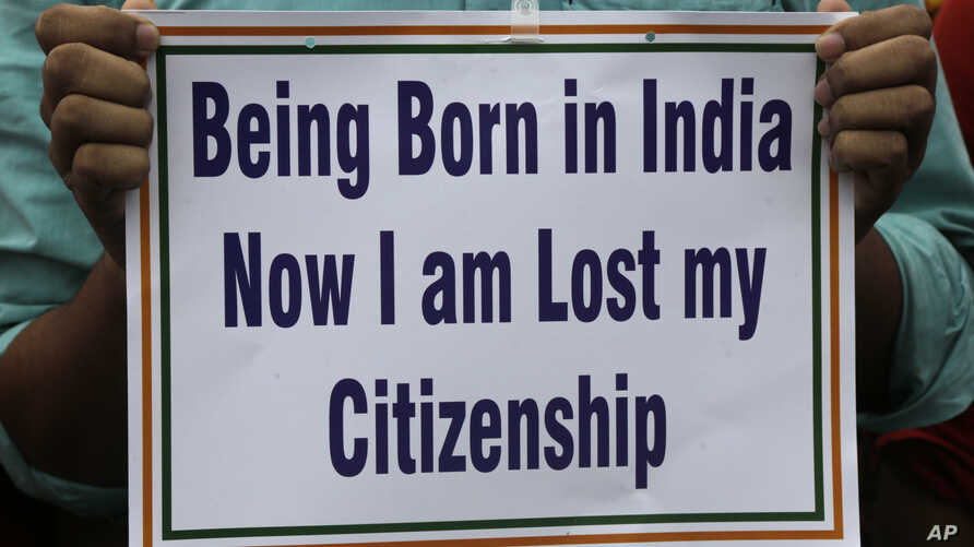 An activist holds a placard during a rally in solidarity with those affected by the final draft of the National Register of Citizens (NRC) in the northeastern state of Assam, in Kolkata, India, Aug. 1, 2018.