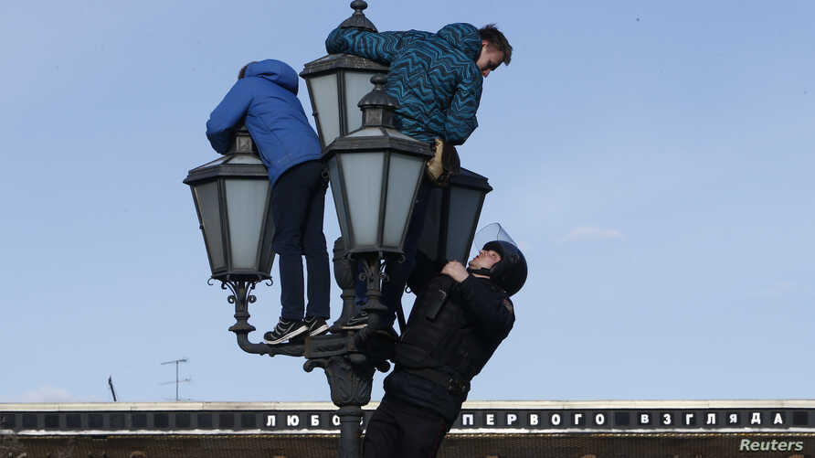 A riot police officer climbs on a lamp pole to detain opposition supporters during a rally in Moscow, Russia, March 26, 2017.