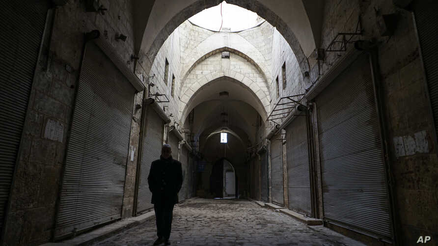 A Syrian man walks through Aleppo's centuries-old market. which still hasn't come back to life more than a year after government forces retook rebel-held neighborhoods around the Old City, Jan. 21, 2018.