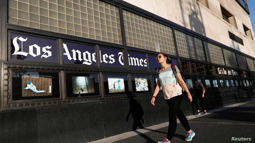 People walk by the Los Angeles Times building in Los Angeles, Feb. 6, 2018.