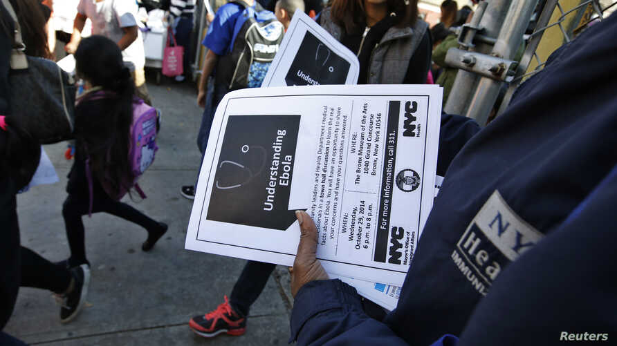 FILE - A New York City Health department official hands out information on the Ebola virus outside a school near a Bronx New York apartment building, Oct. 27, 2014.