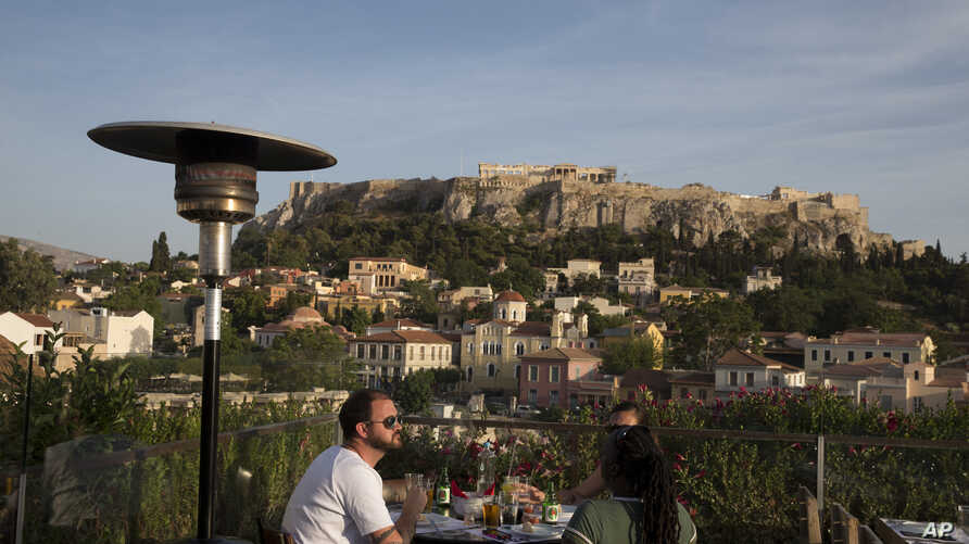 Tourists eat at a restaurant- cafe bar in front of the ancient Acropolis hill in central Athens, Greece, May 31, 2016.