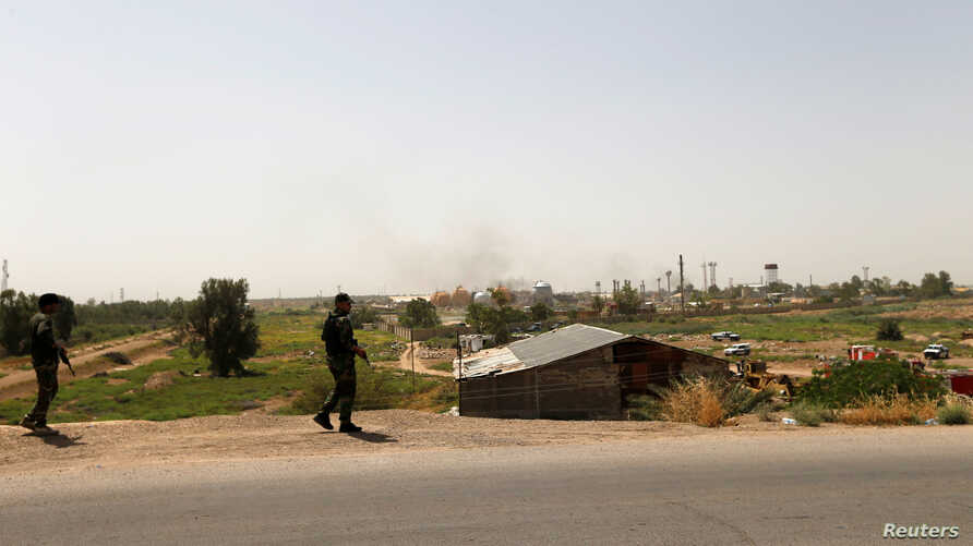 Shi'ite fighters from Saraya al-Salam, who are loyal to radical cleric Muqtada al-Sadr, stand guard on a road after a bomb attack against a state-run cooking gas factory in Taji at Baghdad's northern outskirts, Iraq, May 15, 2016.