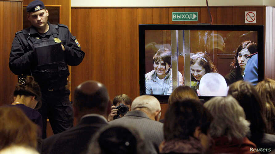 "A bailiff stands in a room as people watch a live broadcast of a court hearing on members of the female punk band ""Pussy Riot"" in Moscow October 10, 2012. The court is hearing an appeal for three members of the band that was adjourned the week before"