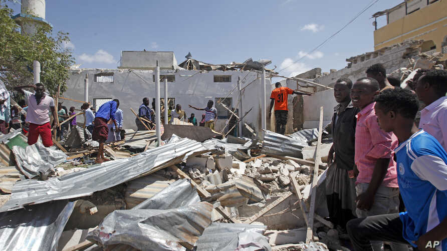 Somalis search for bodies amidst wreckage at the scene of a blast outside the compound of a district headquarters in the capital Mogadishu, Somalia, Sept. 2, 2018.