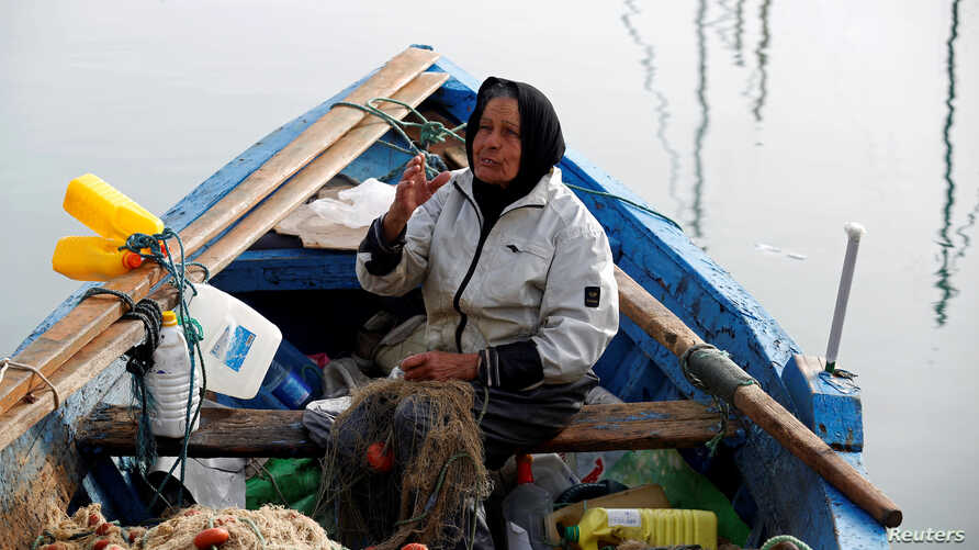 Chrifa Nimri, 69, a fisherwoman, arranges a net after returning from fishing at the seaport Sidi Bou Said, in Tunis, Tunisia, Feb. 23, 2017.